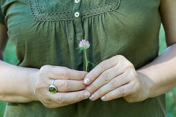 A woman holding a red clover blossom in her hands