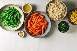 Couscous with parboiled vegetables baby carrots, green beans, sweet corn, spinach in separate ceramic plates with sesame seeds and olive oil