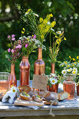 Baguette with floral butter on table decorated with wildflowers in copper-coloured containers