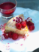 A slice of cream cheesecake with raspberries and edible flowers
