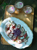 Cured meat rolls with cream cheese filling and edible flowers