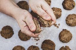 Breaking freshly baked chocolate cookies into halves