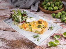 Brussels sprouts and apple quiche with lettuce, cress and sour cream