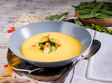 Zucchini curry cream soup with chili, bean sprouts and mangetouts