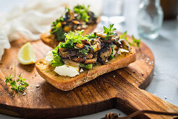 Roasted ciabatta with bryndza, mushroom and kale on a wooden board