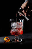 Vermouth poured from a measuring glass into a Negroni cocktail