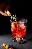 Negroni, served with a rosemary sprig