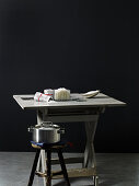 A kitchen table with salt and a pot