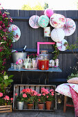 Small drinks table with lanterns and geraniums in garden