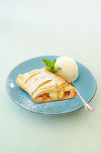 Apple strudel made from puff pastry with vanilla ice cream from a tin
