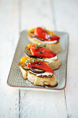 Bruschetta with grilled vegetables and cream cheese on a tray