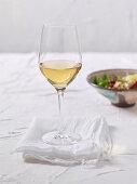 A glass of white wine on a white cloth napkin