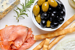 A Mediterranean appetizer platter with cheese, salmon, olives and bread sticks