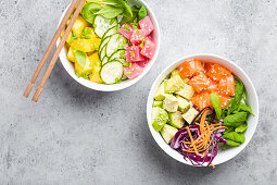 Top view of two assorted poke bowls with fresh raw tuna, salmon, vegetables, fruit