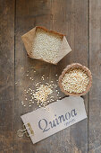 Quinoa, whole and puffed, with a label on a wooden table