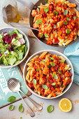Pasta with salmon and veggies in tomato sauce