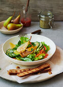 Fruity summer salad with vegetables, pears and wholemeal baguette slices