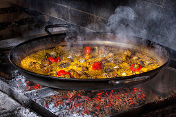 Hot delicious paella with rice, chicken and vegetables cooked in iron pan over open fire