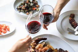Hands clinking with wine glasses while eating delicious meal on white background