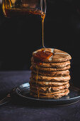 Drizzling hot cross bun pancakes with honey