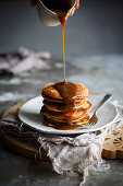 Pancakes being drizzled with caramel sauce