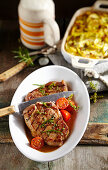 Grilled pork collar steaks in a beer marinade with a potato and beer gratin
