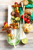 Grilled skewers with meatballs, sausages and vegetables from New Zealand with cherry tomatoes and bread rolls