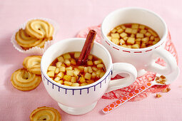 Two cups of hot drinks made with apples, cloves, tea, rock sugar, cinnamon and Calvados served with biscuits