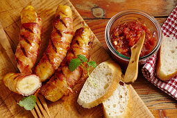 Grilled bananas wrapped in bacon with a tomato and chilli jam and white bread