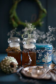 Vintage winter arrangement of two jars of honey decorated with old ribbons