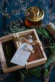 Jar of honey with tag in wooden box as Christmas present