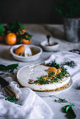 Tasty appetizing decorated with mandarin green and nuts tangerine cake and whole citruses knife bowl with spoon on table