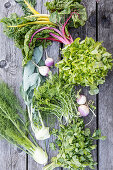 Various garden vegetables, lettuce and herbs on a wooden surface