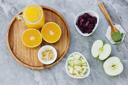 Oranges peanuts and orange juice on table with apples condiment and bowl of beets and apples