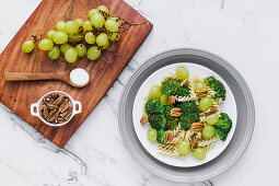 Served bowl of salad with macaroni broccoli and pecans on table with grapes and salt