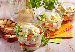 Italian layered salad with pasta, vegetables, yoghurt dressing and mozzarella in preserving jars