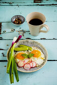 A fried eggs in a plate, served with fresh vegetables and coffee