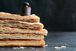 Stacked puff pastry layers with a weight on top