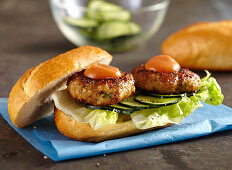 Meatball sandwich with marinated cucumber, lettuce leaves and ketchup