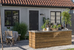Wood-clad island counter in outdoor kitchen outside house