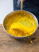 Mixing saffron risotto with butter and parmesan