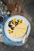 Veganer Mango-Kokos-Cheesecake (Raw Baking) auf Holzstuhl im Freien