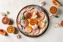 Homemade Cheesecake with sicilian blood oranges, decorated by edible flowers, mint leaves and sugar powder