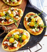 Small homemade pizzas with ricotta, olives, tomatoes and rocket