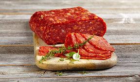 Sliced spicy Italian salami spianata calabria piccante on a wooden board