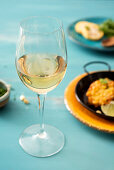 A glass of white wine with a corn fritter in the background