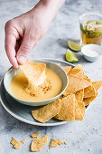 Dipping corn chips in cheese sauce