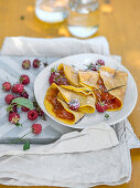 Crepes filled with apricot jam and raspberries
