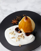 Poached pears with spices served with mascarpone and cream, topped with caramel sauce