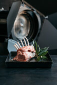 Raw rack of lamb and bay leaves on an oven tray in front of a film lamp